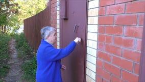 A mulher idosa abre uma porta video estoque