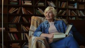 Mulher idosa agradável que senta-se em uma biblioteca home video estoque