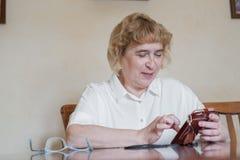A mulher idosa bonita em uma blusa branca que senta-se na tabela e escreve mensagens no telefone A mulher aposentada marcou fotografia de stock royalty free
