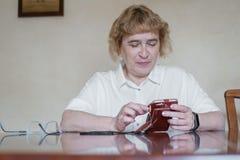 A mulher idosa bonita em uma blusa branca que senta-se na tabela e escreve mensagens no telefone A mulher aposentada marcou fotos de stock royalty free