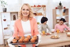 A mulher idosa bonita na blusa cor-de-rosa cozeu queques para os netos que jantam na cozinha fotos de stock