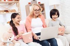 A mulher idosa bonita olha o portátil que ri com seus netos pequenos fotografia de stock