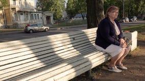Mulher idosa bonito bonita que senta-se em um azul do banco de parque video estoque