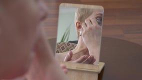 Mulher idosa bonito que olha o espelho e que fricciona a cara com uma fatia de pepino em casa cuidados com a pele cosm?ticos do p vídeos de arquivo