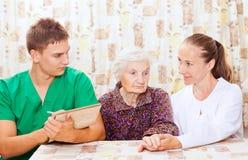 Mulher idosa com os doutores novos Foto de Stock Royalty Free