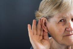 Mulher idosa com perda da audição no fundo cinzento Relativo à idade fotos de stock