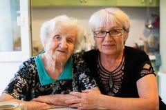 Mulher idosa com sua filha adulta que senta-se em casa foto de stock