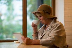 Mulher idosa com tabuleta imagens de stock