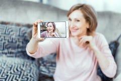 A mulher idosa com um telefone em suas mãos no bom humor está descansando em casa na sala de visitas fotografia de stock