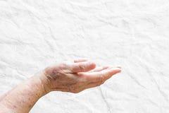 A mulher idosa da mão abre no fundo branco Imagens de Stock