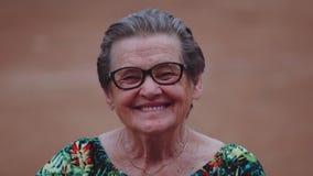 Mulher idosa de sorriso que olha a câmera filme