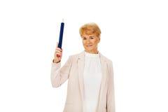 Mulher idosa do sorriso que aponta acima com pena do hege Imagens de Stock