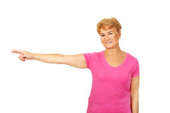 Mulher idosa do sorriso que aponta para o copyspace ou o algo Imagens de Stock