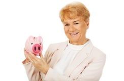 Mulher idosa do sorriso que guarda o mealheiro Imagem de Stock