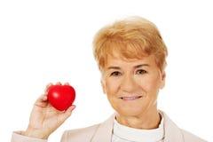 Mulher idosa do sorriso que guarda o modelo do coração Fotografia de Stock