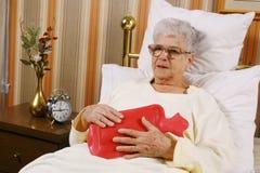 A mulher idosa doente tem uma dor da barriga Imagem de Stock