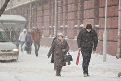 Mulher idosa e homem novo que andam através da neve de condução Blizza foto de stock royalty free