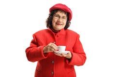 Mulher idosa em uma posição vermelha e em beber do revestimento um café do café fotografia de stock royalty free