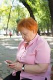 A mulher idosa está chamando pelo telefone no parque da cidade Fotografia de Stock Royalty Free