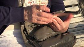 A mulher idosa está estudando a tecnologia da informação através de uma nova geração de tabuleta vídeos de arquivo