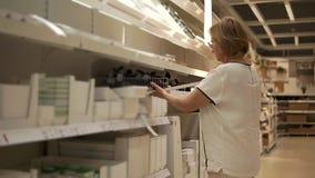 A mulher idosa está explorando a variedade dos acessórios para a cozinha na grande loja video estoque