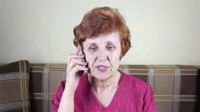 A mulher idosa fala pelo telefone video estoque