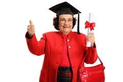 Mulher idosa feliz que guarda um diploma da graduação e que mostra thu foto de stock royalty free