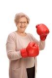 Mulher idosa feliz que veste um par de luvas de encaixotamento imagens de stock royalty free