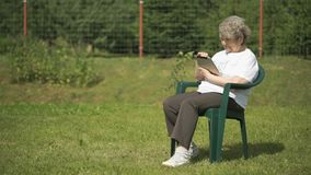 A mulher idosa guarda uma tabuleta do computador fora video estoque