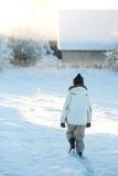 Mulher idosa idosa na roupa morna que anda em casa através das nevadas fortes em uma manhã fria do inverno no nascer do sol Fotos de Stock