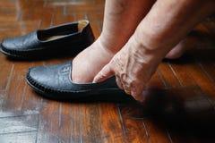 Mulher idosa inchada pés que põem sobre sapatas Fotos de Stock