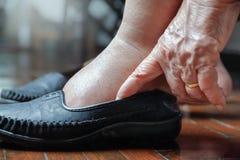 Mulher idosa inchada pés que põem sobre sapatas Imagem de Stock Royalty Free