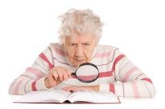 A mulher idosa lê o livro imagem de stock