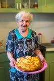 Mulher idosa na cozinha com uma torta em suas mãos passatempo imagens de stock royalty free