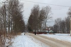 Mulher idosa na estrada do inverno O cão acompanha a mulher Limpado mal Estrada suja É duro ir imagens de stock royalty free