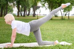 mulher idosa na ioga praticando do sportswear na esteira fotos de stock