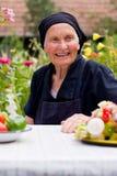 Mulher idosa na tabela Fotos de Stock Royalty Free
