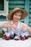 Mulher idosa no chapéu de palha com frascos Imagens de Stock