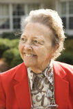 Mulher idosa no revestimento vermelho que sorri ao ar livre Foto de Stock