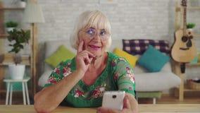A mulher idosa pensativa usa um smartphone que senta-se na tabela na sala de visitas video estoque