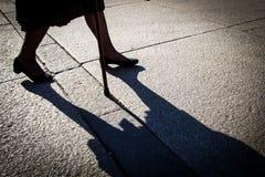 Mulher idosa que anda com bastão Fotos de Stock