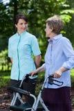 Mulher idosa que anda com um caminhante Fotos de Stock Royalty Free