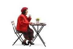 Mulher idosa que bebe uma xícara de café em um café imagem de stock royalty free