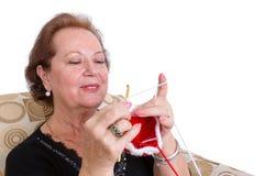 Mulher idosa que concentra-se na sua confecção de malhas Imagens de Stock Royalty Free