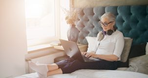 Mulher idosa que datilografa no portátil no quarto video estoque