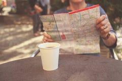 Mulher idosa que estuda o mapa e que come o café Fotografia de Stock