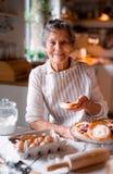 Mulher idosa que faz bolos em uma cozinha em casa imagem de stock