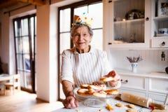 Mulher idosa que faz bolos em uma cozinha em casa Copie o espa?o fotos de stock