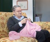 Mulher idosa que faz malha o retrato cor-de-rosa de lãs Imagem de Stock Royalty Free