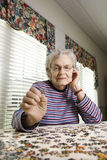 A mulher idosa que faz o gabarito viu o enigma Fotos de Stock Royalty Free
